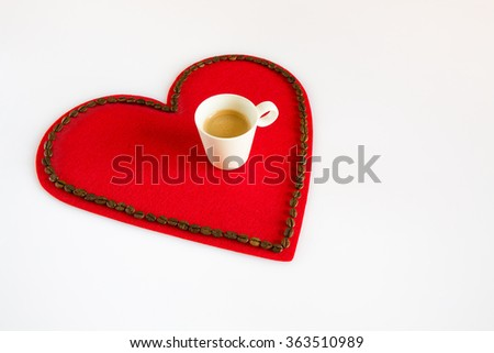 Cup of coffee on a red felt heart with coffee beans around - stock photo