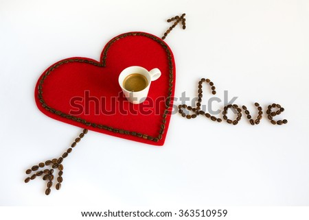 Cup of coffee on a red felt heart with coffee beans around and the word love - stock photo