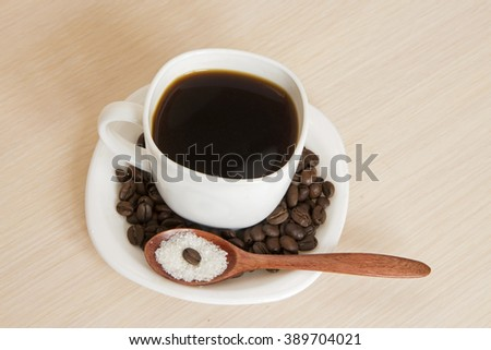 Cup of coffee on a table with a wooden spoon and sugar