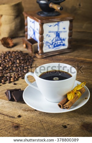 cup of coffee on a textural wooden table with blurred background and grinder