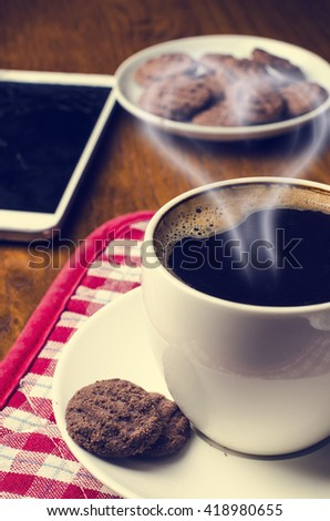 Cup of coffee on a wooden background with mobile phone and cookies. Heart from coffee smog.Warm cup of coffee