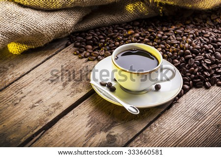 Cup of coffee on aged wooden table - stock photo