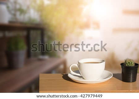 Cup of coffee on an old wooden table outdoor morning time.