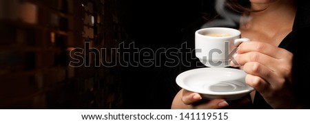Cup of coffee on black background in woman's hands - stock photo