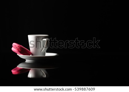 Cup of coffee on black background with macaroon
