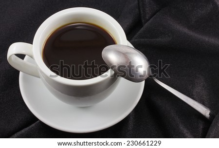 cup of coffee on black fabric - stock photo