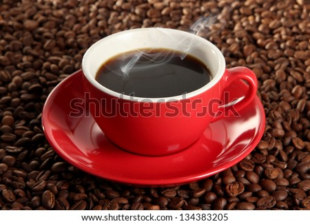 Cup of coffee on coffee beans background - stock photo