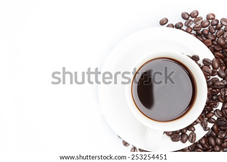 Cup of coffee on coffee beans isolated on white.
