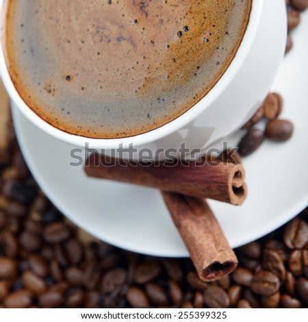 Cup of coffee on saucer and coffee beans - stock photo