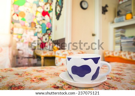 Cup of coffee on table in coffee shop at morning - stock photo