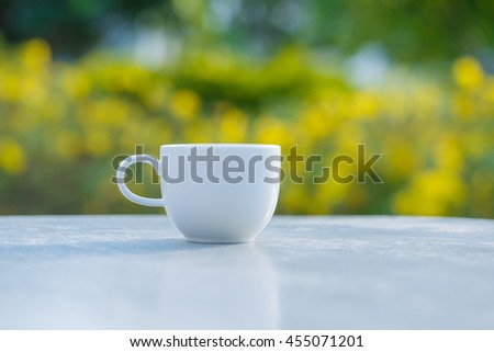 cup of coffee on  table in green garden