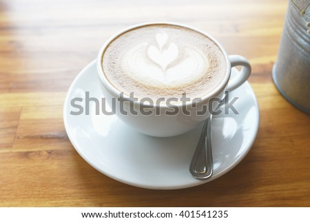 cup of coffee on table leaves and heart shape - stock photo