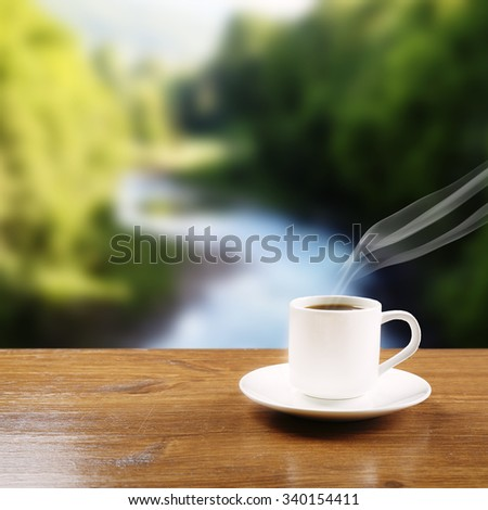 Cup of coffee on table on bright background