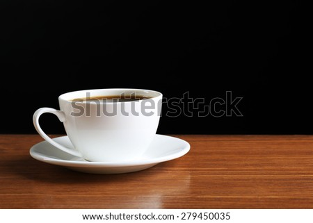 Cup of coffee on table on dark background - stock photo