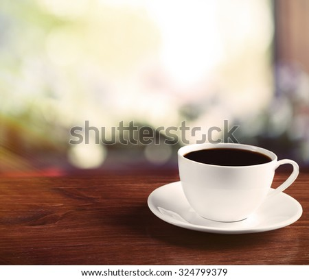 Cup of coffee on table on light background