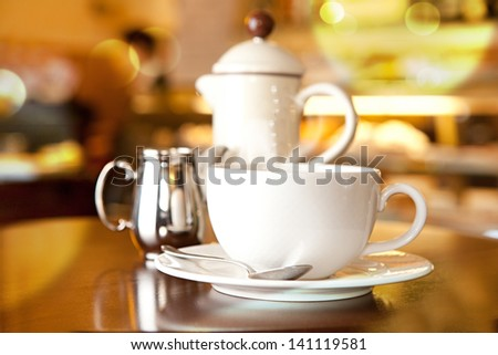 Cup of coffee on table with spoon, creamer and coffee pot - stock photo