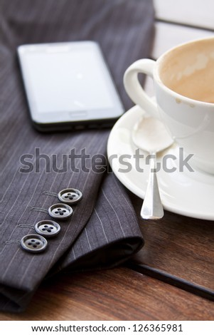 Cup of coffee on table with suit jacket and cell phone in sun concept out of office taking a break mobile office - stock photo