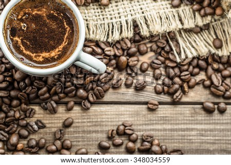 Cup of coffee on the background of black coffee beans, selective focus.