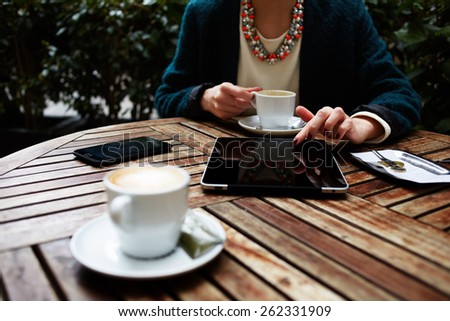 Cup of coffee on the foreground with elegant woman using busy touch screen tablet at the coffee shop wooden table, bill check and mobile phone near - stock photo