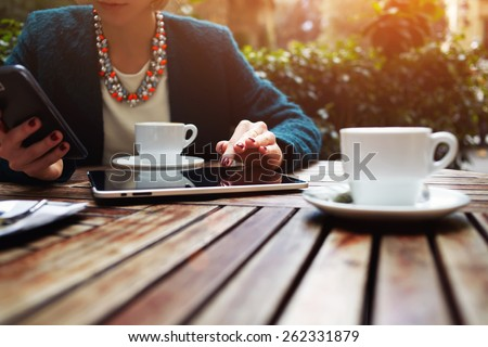 Cup of coffee on the foreground with elegant young woman using busy touch screen tablet at the coffee shop wooden table, work break of business people, flare sun light - stock photo