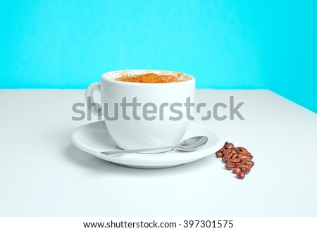 cup of coffee on the table with beans on a blue background - stock photo