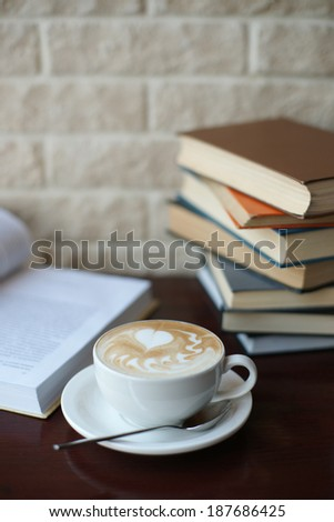Cup of coffee on the table with books