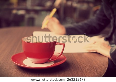 Cup of coffee on the wood texture background in vintage color tone