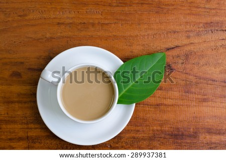 Cup of coffee on the wooden floor