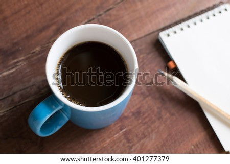 cup of coffee on wood table with notepad