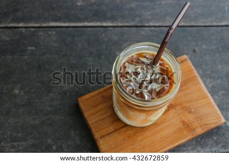 Cup of coffee on wooden table - Ice latte coffee - stock photo