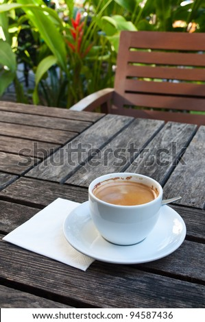 Cup of coffee on wooden table in the garden - stock photo