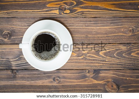Cup of coffee on wooden table in top view - stock photo