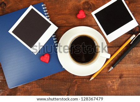 Cup of coffee on worktable covered with photo frames close up - stock photo