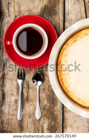 Cup of coffee or tea with fresh baked cheesecake on wooden table. Breakfast eating background. Top view image - stock photo