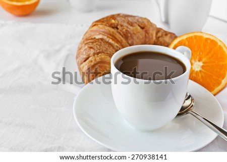 Cup of coffee,orange and croissant.