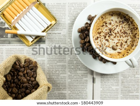 Cup of coffee, roasted beans and cigarettes arranged on a newspaper - stock photo