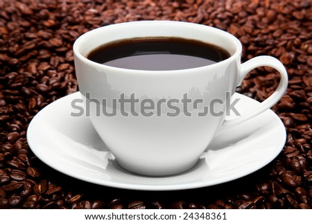 Cup of coffee sitting in a bed of coffee beans isolated over a white background