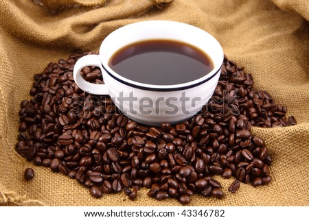 Cup of coffee sitting in a bed of coffee beans on top of a canvas bag
