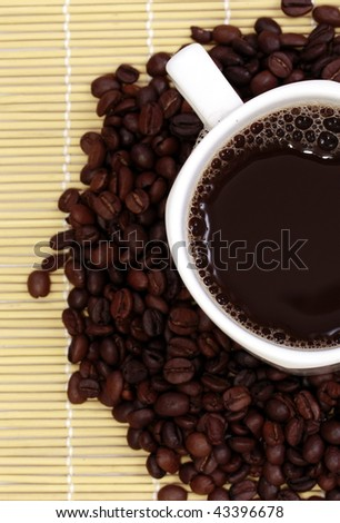 Cup of coffee sitting on coffee beans