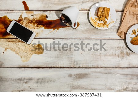 Cup of coffee spilled on wooden table - stock photo