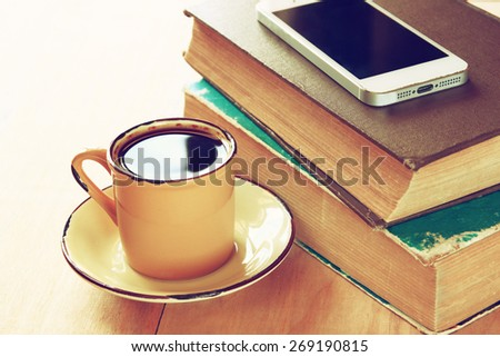 cup of coffee, stack of old books and smartphone over wooden table, retro filtered image  - stock photo