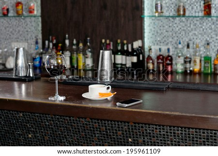 Cup of coffee standing on a bar counter alongside a half empty glass of red wine after a customer has tried to sober up before leaving for home - stock photo
