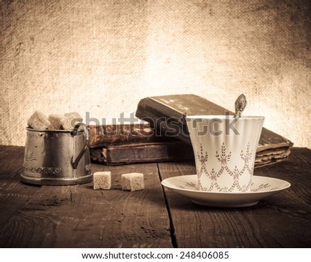 Cup of coffee, sugar bowl and stack of old books on the old wooden table.