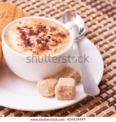 Cup of coffee, sweets and cane sugar cubes, square. Coffee concept. Selective focus. - stock photo