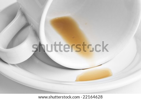 Cup of coffee turned on its side with only a few drops of coffee left. - stock photo