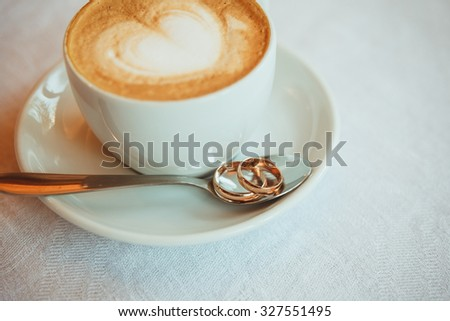 Cup of coffee, wedding rings in spoon on table - stock photo