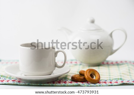 Cup of coffee with bagels, tea pot on a napkin.