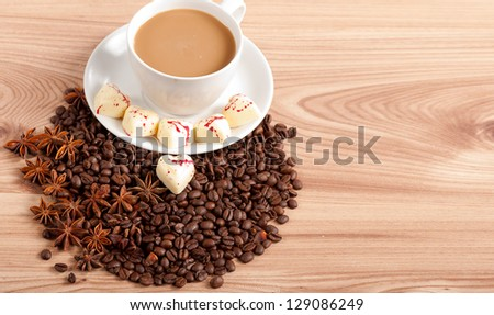 Cup of coffee with beans and white chocolate heart candy  over wooden background. - stock photo