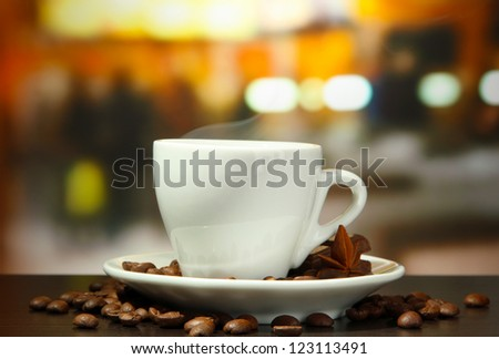 cup of coffee with beans on table in cafe - stock photo