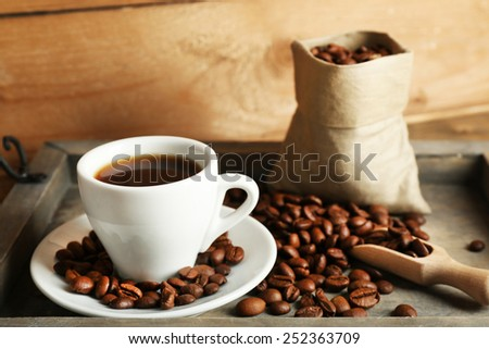 Cup of coffee with beans on tray and rustic wooden background - stock photo